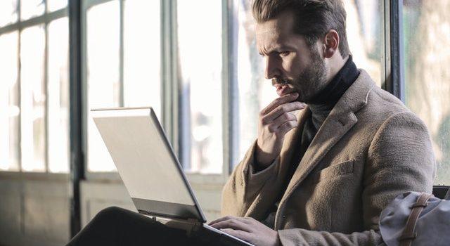 man-wearing-brown-jacket-and-using-laptop