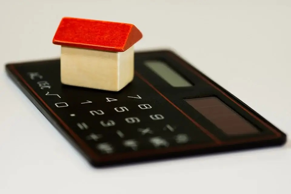 small toy house on top of calculator
