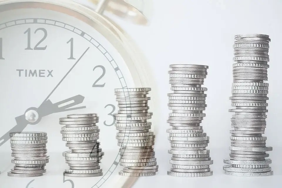 stacks of coins in front of clock