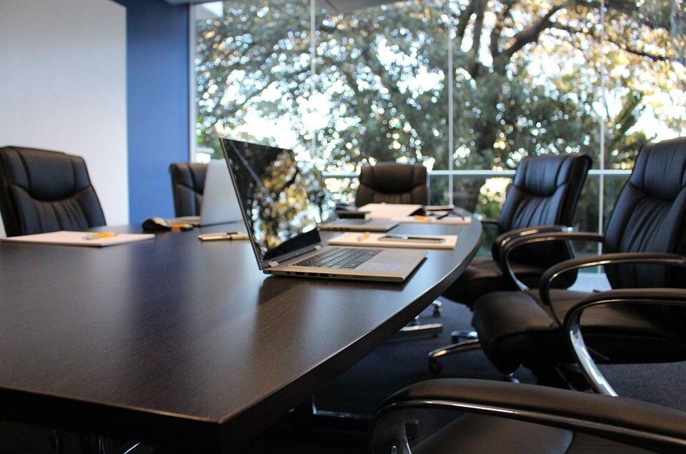 large meeting table with open laptops